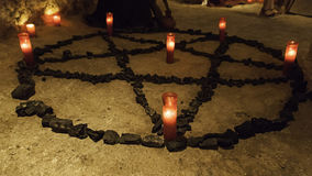 Satanic pentacle with lighted candles. Dark magic ritual detail, occultism Royalty Free Stock Photo