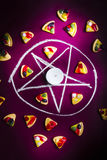 Satanic symbol of pizza sacrifice. Black magic in practise with a occult satanic symbol into pizza sacrifice on purple background Stock Images