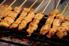 satay的猪肉肉在木炭火焰用卤汁泡与椰奶和辣椒混合物然后被烤 免版税库存图片