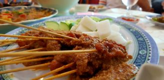 Satay. Chicken satay with lontong and cucumber Stock Image