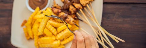 Satay da galinha servido com molho do amendoim e batatas fritas Bali, BANDEIRA do estilo de vida, formato longo Imagens de Stock Royalty Free
