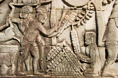 Satay kebab cooking, Ancient sculpture, Angkor, Ca. Ancient Khmer bas relief sculpture showing satay kebabs being grilled on a fire.  Frieze on a wall of Bayon Stock Photos