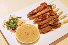 Satay meat in thick sticks with sweet peanut sauce & sliced raw vegetables at side Royalty Free Stock Photo
