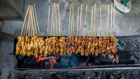 Satay or sate is an Indonesian and Malaysian dish consisting of small pieces of meat. Grilled on a skewer and served with a spiced sauce that typically contains stock image