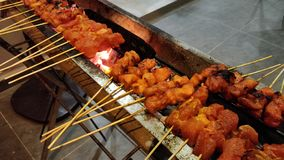Satay or sate. Satay, or sate in Indonesian spelling, is a dish of seasoned, skewered and grilled meat, served with a sauce. It is a dish of Southeast Asia royalty free stock image