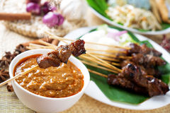 Satay or sate. Skewered and grilled meat, served with peanut sauce, cucumber and ketupat. Traditional Malay food. Malaysian dish, Asian cuisine stock photo
