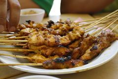 Satay or sate. Skewered and grilled meat, served with peanut sauce, cucumber and ketupat. Traditional Malay food. Malaysian dish, Asian cuisine Royalty Free Stock Photos
