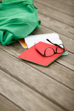 Satchel with notebooks for study and glasses lying. On wooden floor.school accessories Stock Images