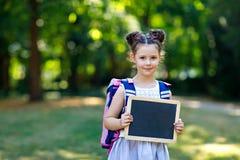 Счастливое положение девушки маленького ребенка со столом и рюкзаком или satchel Schoolkid на первый день элементарного класса Зд стоковые изображения rf