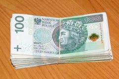 Satck av 100 PLN - polska pengar med ett gummi på träbakgrunden Royaltyfri Foto