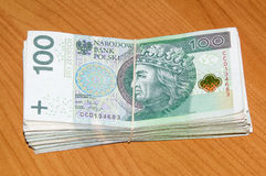 Satck of 100 PLN - polish money with a rubber on the wooden background. Royalty Free Stock Photo