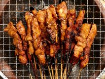 Sate Ayam on Earthenware Stove. Indonesian chicken satays being barbecued using charcoal on traditional earthenware stove Stock Photo