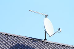 Satelite with antena. White satelite with antena and internet connection on grey roof Royalty Free Stock Image