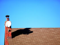 Satelite Dish. Casing a shadow onto a roof top Royalty Free Stock Images