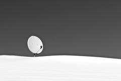 Satellietantenne op sneeuwdak in zwart-wit stock afbeeldingen