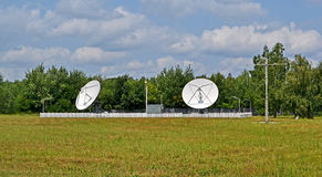 Satellietantennes, groene bomen en onweersbui blauwe hemel, Stock Fotografie