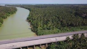 Satellietbeeld die van vervoer zich langs brug boven tropische groene gekleurde rivier in Thailand bewegen Infrastructuur in Azia stock videobeelden