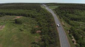 Satellietbeeld die van witte vrachtwagen de bezige brug van de het viaductoverdrive van de wegweg overgaan De auto's en de vracht stock footage