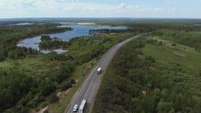 Satellietbeeld die van witte vrachtwagen de bezige brug van de het viaductoverdrive van de wegweg overgaan De auto's en de vracht stock video
