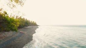 Satellietbeeld met overzees en strand in Noord-Bali bij zonsondergang stock video