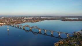 Satellietbeeld op de herfstlandschap van spoorwegbrug boven Dnieper-rivier in Dnipro-stad stock video