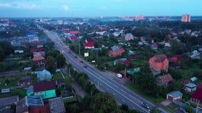 Satellietbeeld op een weg met voertuigen die door een dorp overgaan stock videobeelden