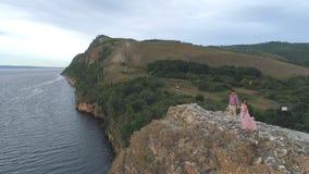 Satellietbeeld op Jong paar die zich op klippen rond het overzees en de rotsen bevinden stock video