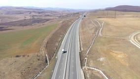 Satellietbeeld van auto's en vrachtwagens die een weg, hommelschot doorgeven stock videobeelden