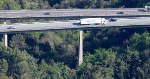Satellietbeeld van auto's en vrachtwagensverkeer op een wegbrug met pijlers stock footage
