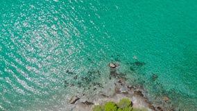 Satellietbeeld van blauwe overzeese oppervlakte op rotsachtige kust met lichte bezinningen Hoogste mening van transparant turkooi stock videobeelden