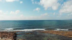 Satellietbeeld van blauwe toneeloverzees en rotsachtige kustlijn met sterke golven die de kust raken die het schuim bespatten stock video