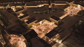 Satellietbeeld van dakbovenkanten van aangestoken gebouwen van winkelcentrum in de winterdag stock footage