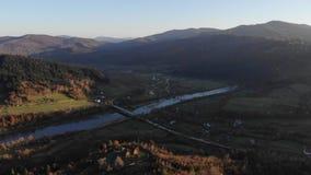 Satellietbeeld van de herfstlandschap: bergen, bossen en rivier Comfortabele houten buitenhuizen op de hellingen Karpatische Berg stock video