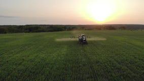 Satellietbeeld van de landbouwtractor het bespuiten op gebied met spuitbus, herbiciden en pesticiden bij zonsondergang Landbouwbe stock videobeelden