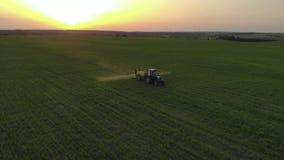 Satellietbeeld van de landbouwtractor het bespuiten op gebied met spuitbus, herbiciden en pesticiden bij zonsondergang Landbouwbe stock video