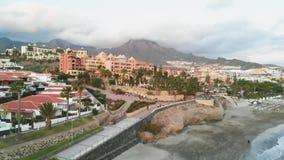 Satellietbeeld van de schilderachtige Spaanse stad bij zonsondergang op de kust van het eiland van Tenerife Adeje, Spanje stock footage