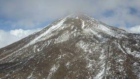 Satellietbeeld van de top van de Teide-vulkaan op Tenerife, die met sneeuw en wolken wordt behandeld stock videobeelden