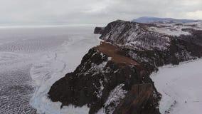 Satellietbeeld van de winterlandschap van rotsachtige bergen op meer Baikal stock videobeelden