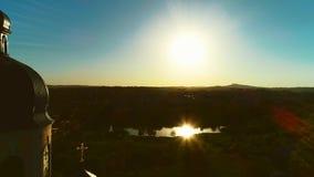 Satellietbeeld van dichte omhooggaande kerkkoepel en verbazende zonsondergang De zon wordt weerspiegeld in weinig meer 4K stock footage