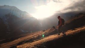 Satellietbeeld van een episch schot van een meisje die op de rand van een berg als silhouet in een mooie zonsondergang lopen stock footage