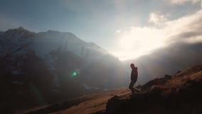 Satellietbeeld van een episch schot van een mens die op de rand van een berg als silhouet in een mooie zonsondergang lopen Silhou stock footage