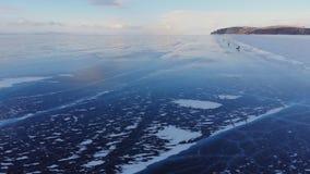 Satellietbeeld van een groep reizigers die op het ijs van een bevroren meer schaatsen stock videobeelden