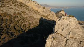 Satellietbeeld van een jonge vrouw die zich op de bovenkant van een berg tegen het overzees bevinden Dame op de top in mooi lands stock video