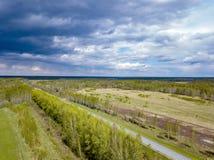 Satellietbeeld van een landschap met een weg op een gebied onder groene bomen onder een grijze hemel met wolken v??r de regen bui royalty-vrije stock foto