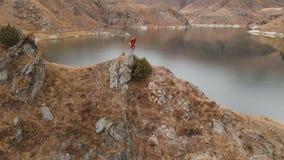 Satellietbeeld van een meisje die zich op een rots op de kust van een meer bevinden, dat het landschap op haar DSLR-camera fotogr stock video
