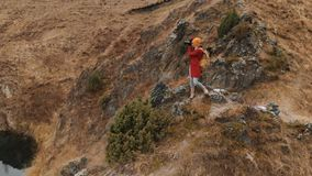 Satellietbeeld van een meisje die zich op een rots op de kust van een meer bevinden, dat het landschap op haar DSLR-camera fotogr stock videobeelden
