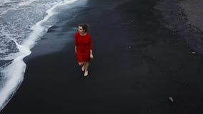 Satellietbeeld van een meisje in een rode kleding die op het strand met zwart zand lopen Tenerife, Canarische Eilanden, Spanje