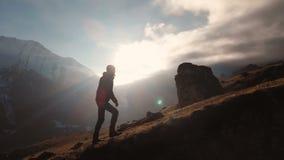 Satellietbeeld van episch schot van een mens die op de rand van de berg als silhouet in een mooie zonsondergang lopen Silhouet stock video