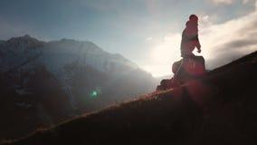 Satellietbeeld van episch schot van een mens die op de rand van de berg als silhouet in een mooie zonsondergang lopen Silhouet stock footage