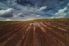 Satellietbeeld van gebied van de tractor het bespuitende wijngaard met fungicide royalty-vrije stock foto